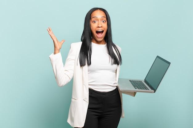 Молодая черная женщина чувствует себя счастливой, удивленной и веселой, улыбается с позитивным настроем, реализует решение или идею. концепция ноутбука