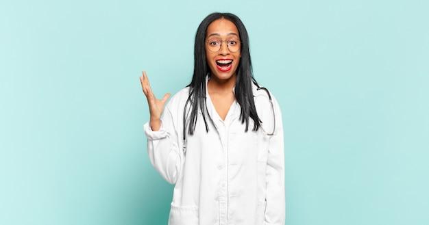 젊은 흑인 여성이 행복하고 놀라움과 쾌활한 느낌, 긍정적 인 태도로 웃고 솔루션이나 아이디어를 실현합니다. 의사 개념