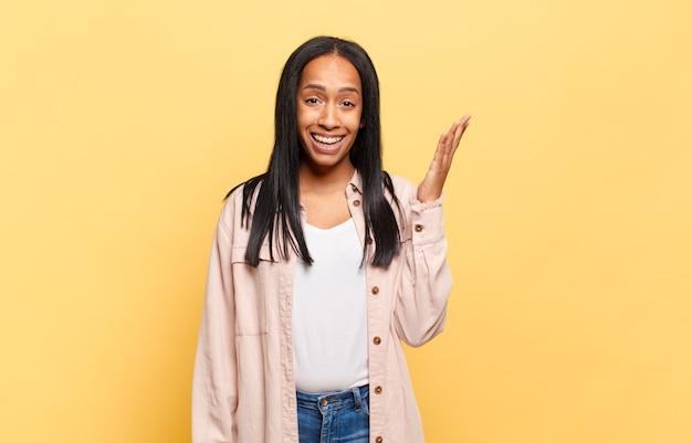 Молодая черная женщина чувствует себя счастливой, удивленной и веселой, улыбается с позитивным настроем, реализует решение или идею
