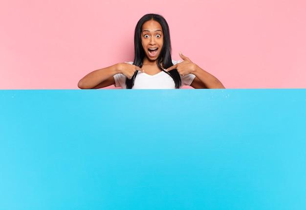 Молодая черная женщина чувствует себя счастливой, удивленной и гордой, указывая на себя взволнованным, изумленным взглядом. копировать космическую концепцию