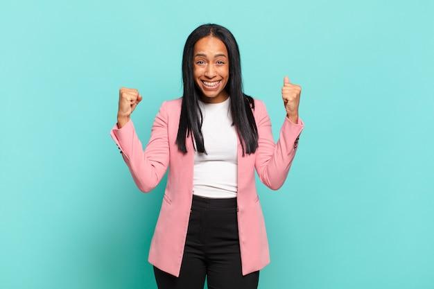 Молодая черная женщина чувствует себя счастливой, удивленной и гордой, кричит и празднует успех с широкой улыбкой.