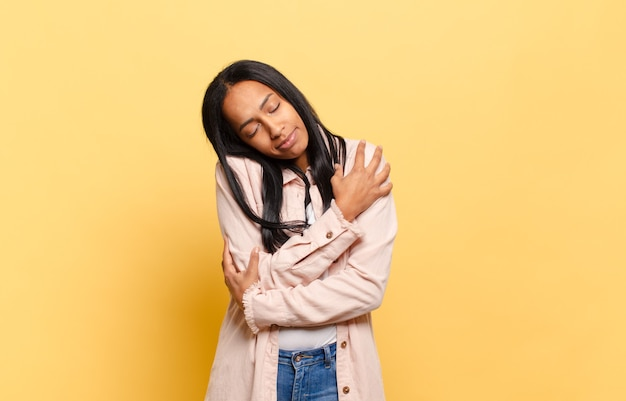 Молодая темнокожая женщина чувствует себя влюбленной, улыбается, обнимает и обнимает себя, остается одинокой, эгоистичной и эгоцентричной