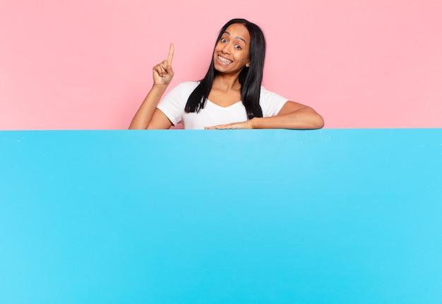 Молодая чернокожая женщина чувствует себя счастливым и взволнованным гением, реализовав идею, весело подняв палец, эврика !. копировать космическую концепцию