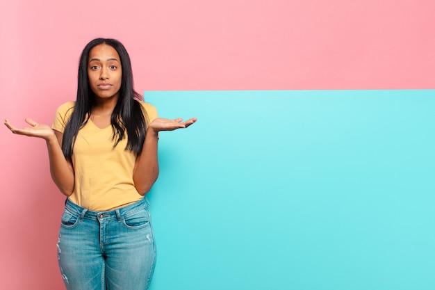 젊은 흑인 여성이 의아해하고 혼란스럽고 의심스럽고 가중하거나 재미있는 표현으로 다른 옵션을 선택하는 느낌. 복사 공간 개념