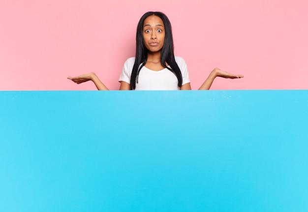 젊은 흑인 여성은 어리둥절하고 혼란스러워하고, 의심하고, 가중치를 두거나, 재미있는 표정으로 다른 옵션을 선택합니다. 복사 공간 개념