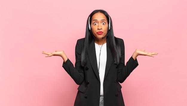 若い黒人女性は、戸惑い、混乱し、疑ったり、重みを付けたり、面白い表現でさまざまなオプションを選択したりします。テレマーケティングの概念