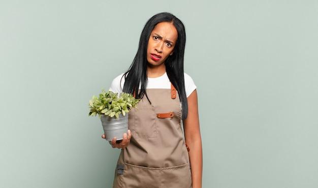 젊은 흑인 여성이 의아해하고 혼란스러워하며 예상치 못한 것을 바라 보는 멍청하고 기절 한 표정으로. 정원사 개념
