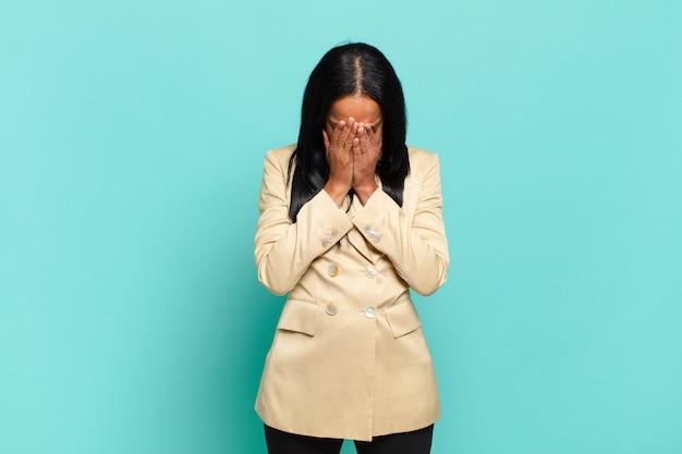 Молодая темнокожая женщина чувствует себя грустной, разочарованной, нервной и подавленной, закрывает лицо обеими руками и плачет. бизнес-концепция