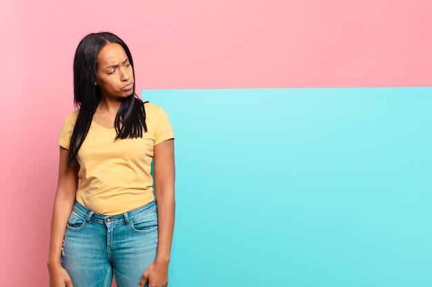 젊은 흑인 여성이 슬프고 화 나거나 화가 나고 부정적인 태도로 측면을 바라보고 의견이 일치하지 않습니다. 복사 공간 개념