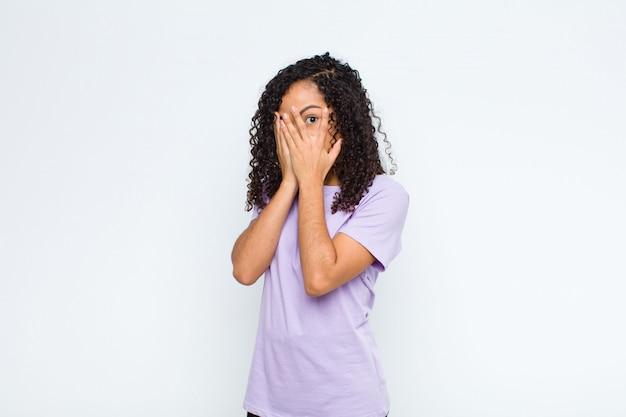 Молодая негритянка чувствует себя испуганной или смущенной, заглядывает или шпионит глазами, наполовину прикрытыми руками к белой стене