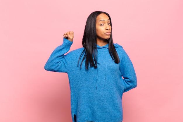 深刻で、強く、反抗的であると感じ、拳を上げ、抗議し、革命のために戦う若い黒人女性