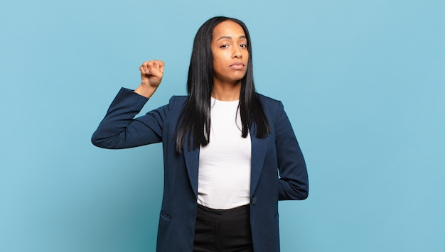 Young black woman feeling serious, strong and rebellious, raising fist up, protesting or fighting for revolution. business concept