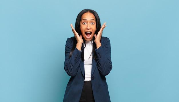 Молодая черная женщина чувствует себя потрясенной и взволнованной, смеющейся, пораженной и счастливой из-за неожиданного сюрприза. бизнес-концепция