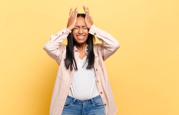 若い黒人女性は、ストレスと不安を感じ、頭痛で落ち込んで欲求不満を感じ、両手を頭に上げます