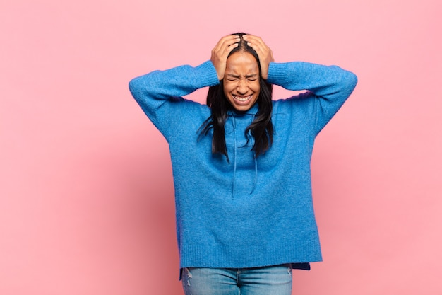 Young black woman feeling stressed and frustrated, raising hands to head, feeling tired, unhappy and with migraine