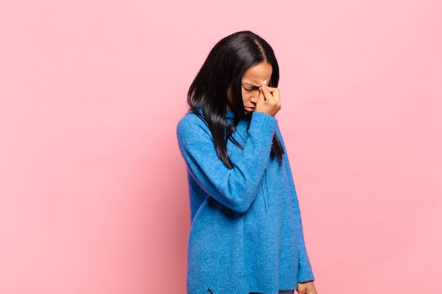Молодая чернокожая женщина чувствует стресс, несчастье и разочарование, трогает лоб и страдает от сильной мигрени