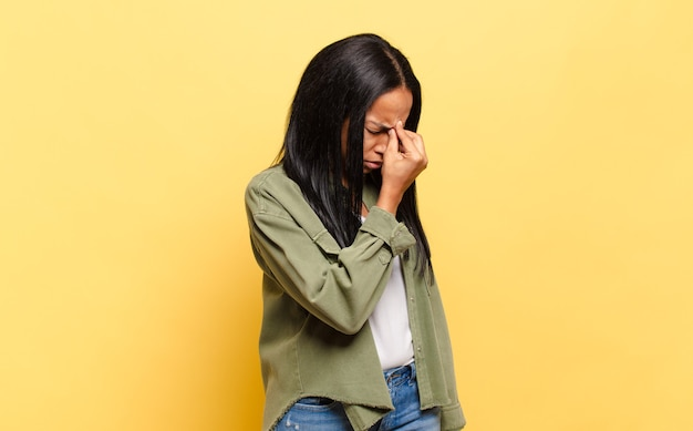 Young black woman feeling stressed, unhappy and frustrated, touching forehead and suffering migraine of severe headache