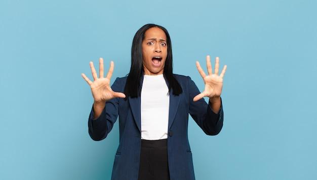 Молодая темнокожая женщина чувствует себя ошеломленной и напуганной, боится чего-то пугающего, с раскрытыми руками и говорит: «держись подальше». бизнес-концепция