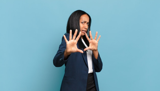 Young black woman feeling terrified, backing off and screaming in horror and panic, reacting to a nightmare. business concept
