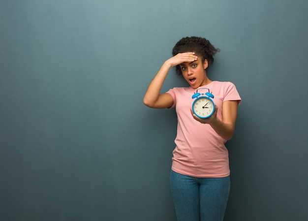 Young black woman forgetful, realize something. she is holding an alarm clock.