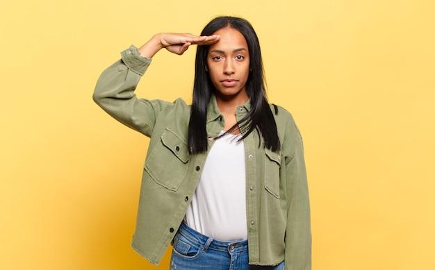 존경을 표시하는 명예와 애국심의 행동에서 군사 경례와 함께 카메라를 인사하는 젊은 흑인 여성