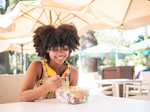 Молодая черная женщина ест свежий салат, сидя на столе на улице, концепция здорового питания