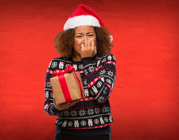 Young black woman holding a gift in christmas day biting nails, nervous and very anxious