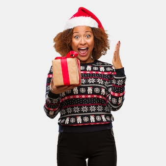 Young black woman holding a gift in christmas day celebrating a victory or success