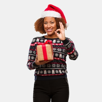 Young black woman holding a gift in christmas day cheerful and confident doing ok gesture