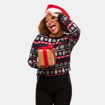 Young black woman holding a gift in christmas day confident doing ok gesture on eye