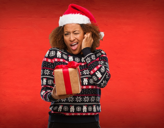 Young black woman holding a gift in christmas day covering ears with hands