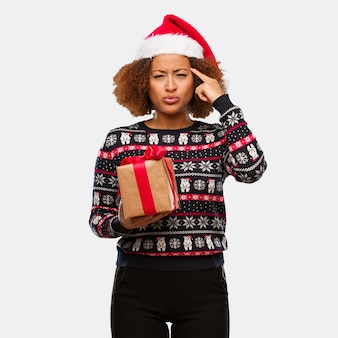 Young black woman holding a gift in christmas day doing a concentration gesture