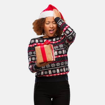Young black woman holding a gift in christmas day forgetful, realize something