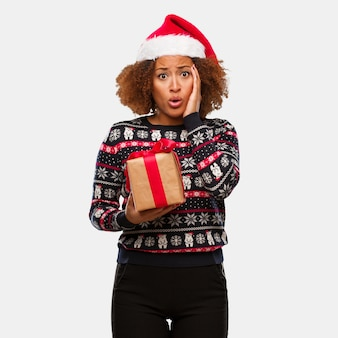 Young black woman holding a gift in christmas day surprised and shocked