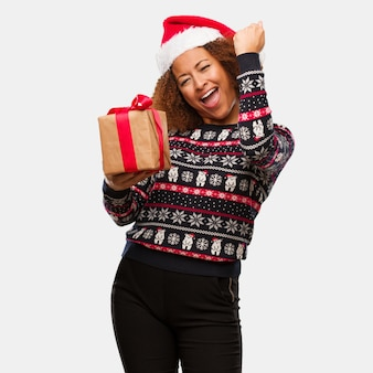 Young black woman holding a gift in christmas day who does not surrender