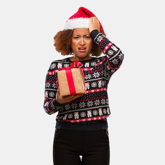 Young black woman holding a gift in christmas day worried and overwhelmed
