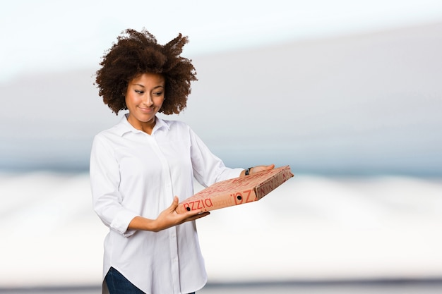 Young black woman holding a pizza box