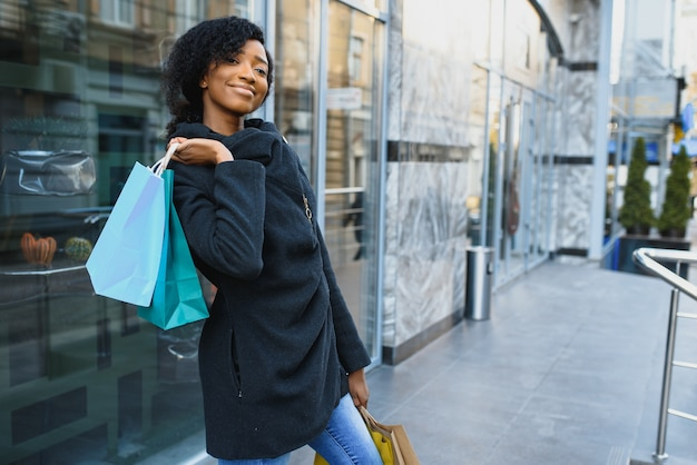 Young black woman holding shopping bags