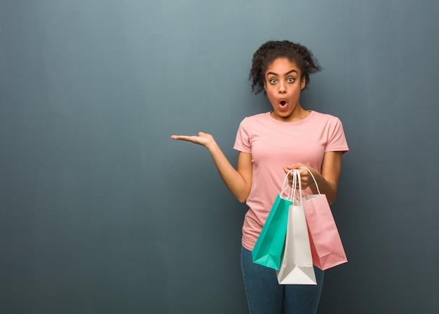 손바닥 손에 뭔가 들고 젊은 흑인 여성. 그녀는 쇼핑백을 들고있다.