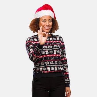 인쇄 명랑하고 자신감을 확인 제스처와 트렌디 한 크리스마스 스웨터에 젊은 흑인 여성