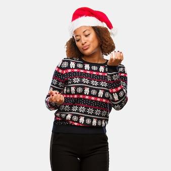 인쇄 혼란과 의심과 트렌디 한 크리스마스 스웨터에 젊은 흑인 여성