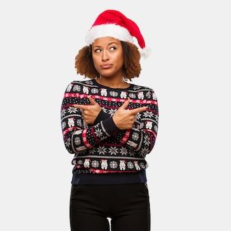 인쇄 유행 크리스마스 스웨터에 젊은 흑인 여성이 두 가지 옵션 사이에서 결정