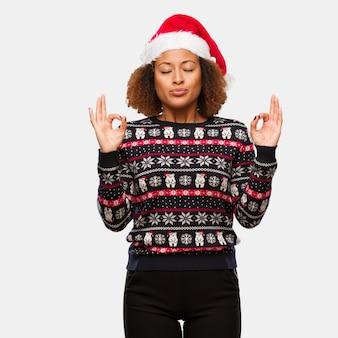 인쇄 요가 수행하는 유행 크리스마스 스웨터에 젊은 흑인 여성