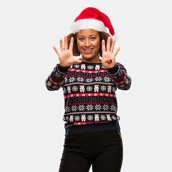 인쇄 번호 9를 보여주는 트렌디 한 크리스마스 스웨터에 젊은 흑인 여성