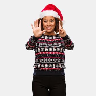 인쇄 번호 6을 보여주는 트렌디 한 크리스마스 스웨터에 젊은 흑인 여성