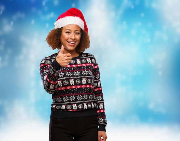 인쇄 미소와 엄지 손가락을 올리는 유행 크리스마스 스웨터에 젊은 흑인 여성