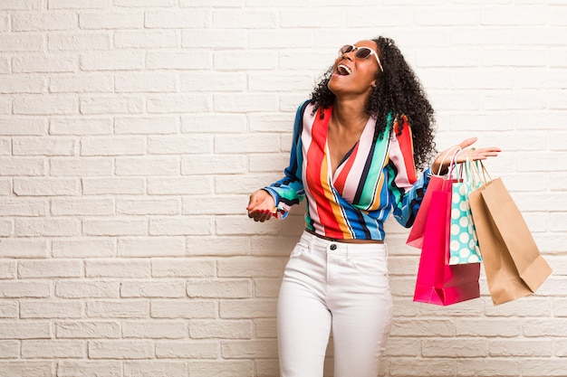 Young black woman laughing and having fun, being relaxed and cheerful