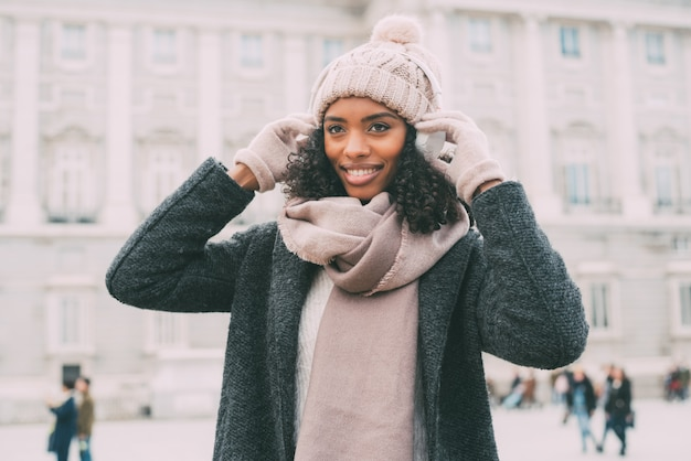 Young black woman listening to music and dancing on the mobile phone near the royal palace in winter