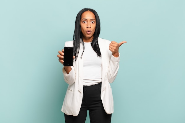 Young black woman looking astonished in disbelief, pointing at object on the side and saying wow, unbelievable. smart phone concept