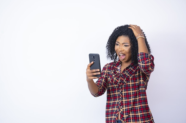 悩んで心配そうに見える彼女の電話を見ている若い黒人女性